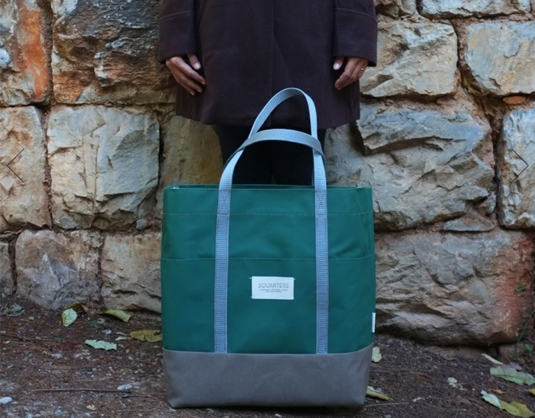 Woman holding a sustainable 3Quarters bag in front of a stone wall