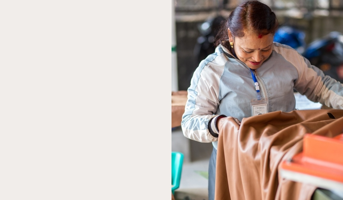 Woman holding a piece of leather in a factory