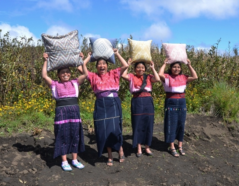 Four women artisans holding their handmade products