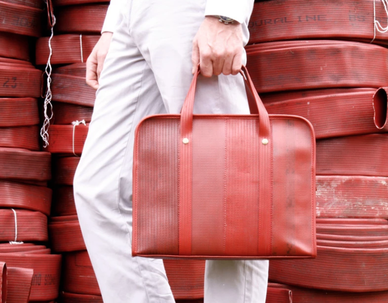 Person holding Elvis & Kresse upcycled bag in front of a stack of hose pipes