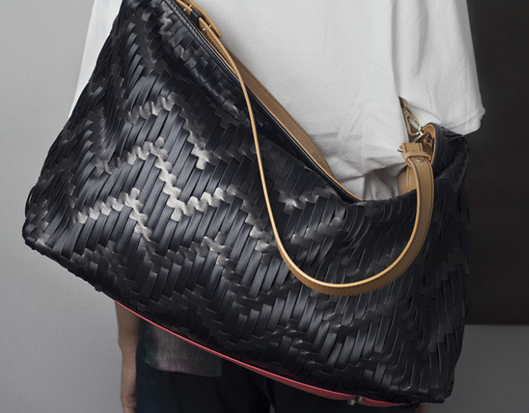 MWOVEN bag over the shoulder of someone facing a wall.
