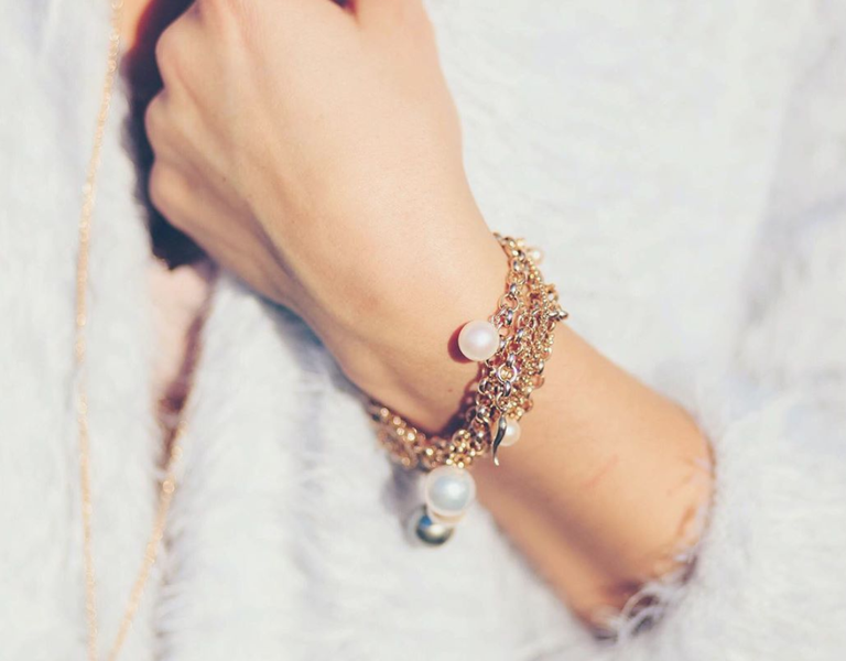 The arm of a woman wearing an ORA pearl bracelet and necklace in the background