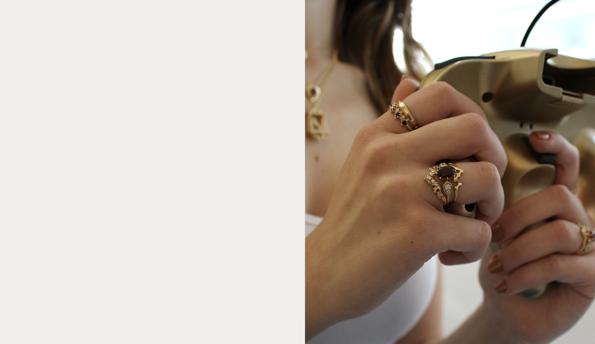 Woman holding a gaming console wearing Soulbound sustainable rings and necklace.