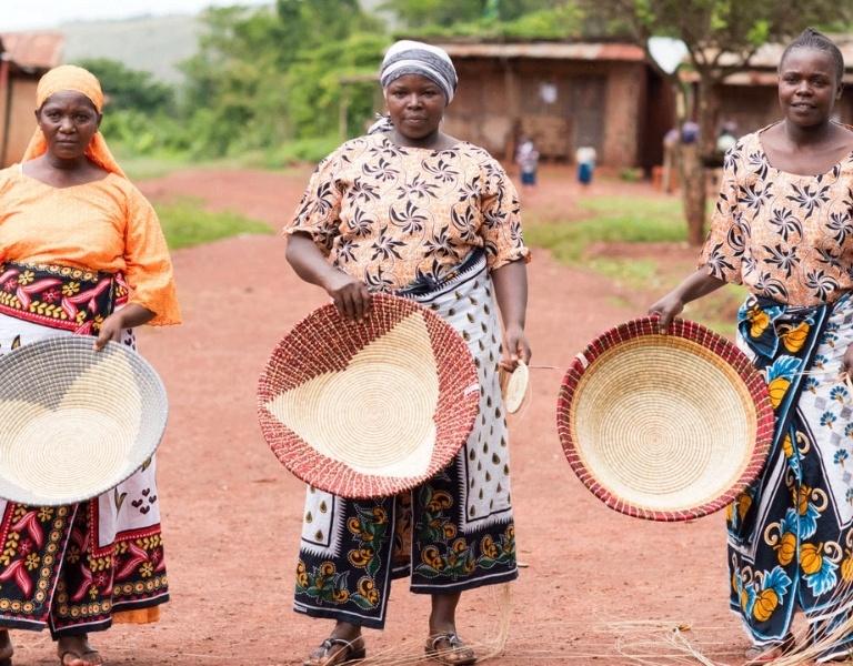 Three women artisans holding their handmade products