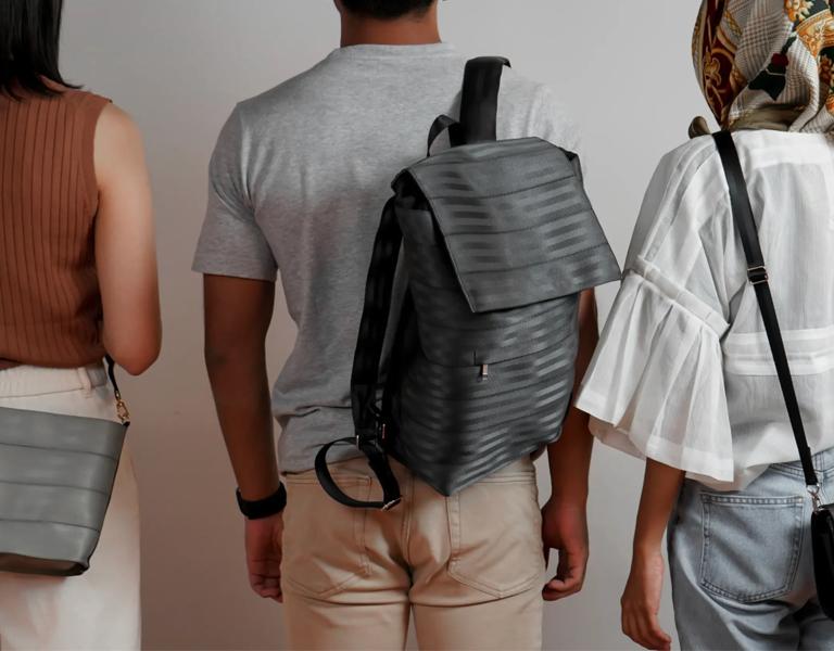 3 people stood with their backs to the camera wearing Biji Biji bags