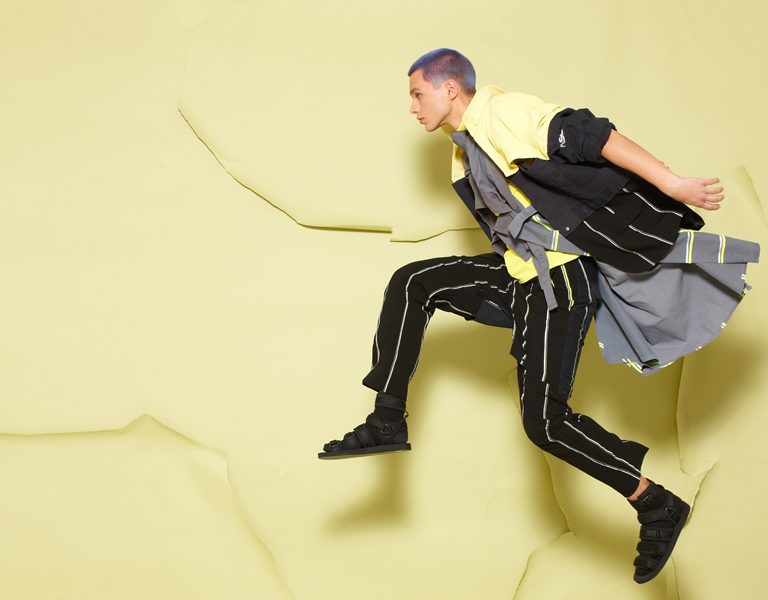 Image of a male model leaping in the air, wearing upcycled clothes made by Israeli designer Natalie Tzur, against a yellow backdrop of torn paper.
