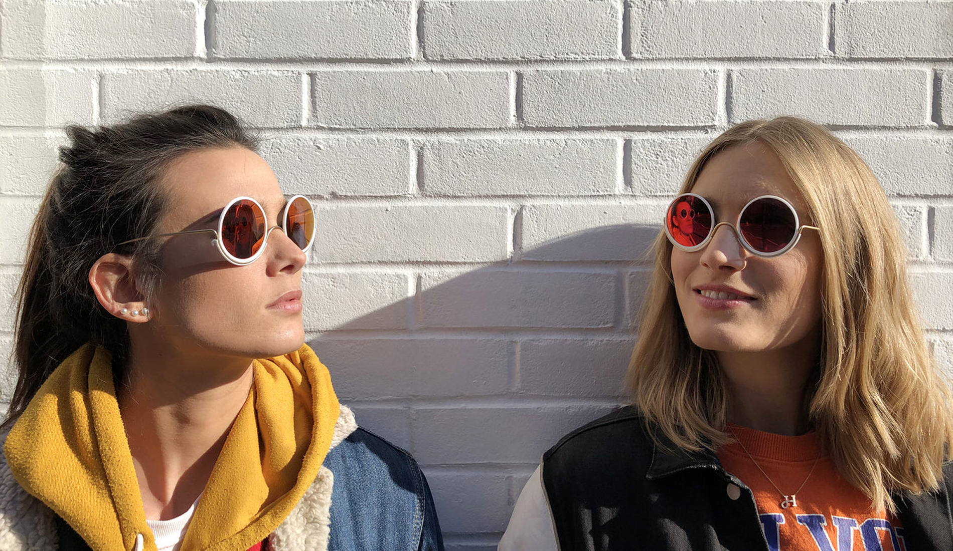 image of two women wearing Wire Glasses sunglasses leaning against a white brick wall
