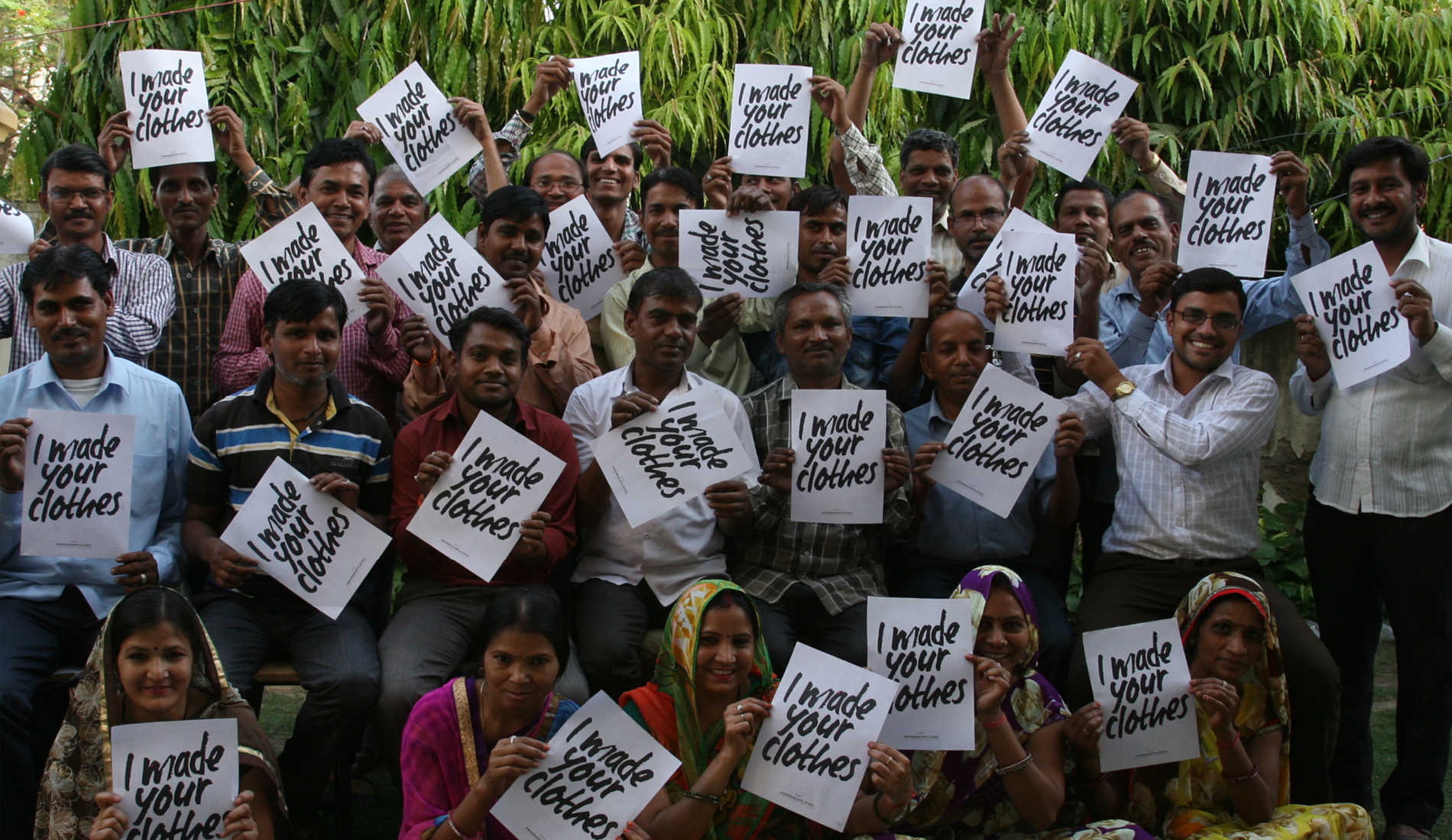 Factory workers holding up posters with the  #imadeyourclothes